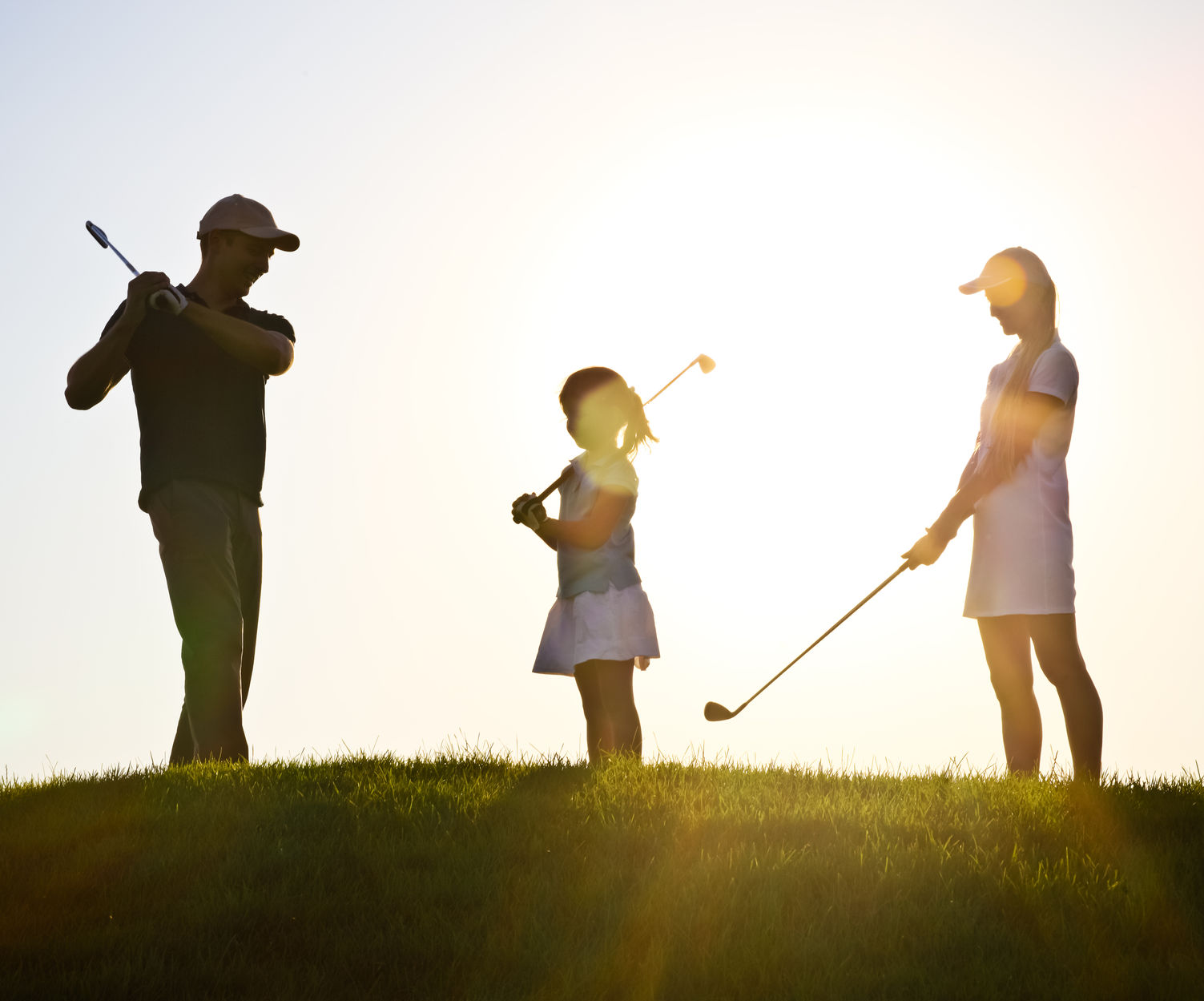 31763468 - family of a golfers playing golf at sunset